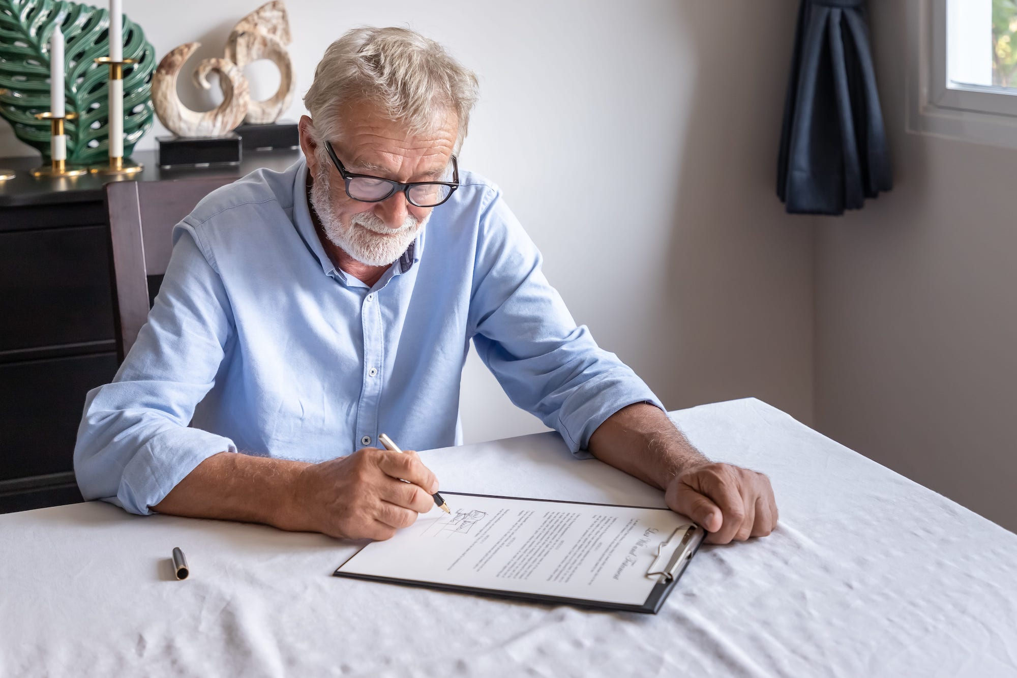 Senior man with clipboard signing document